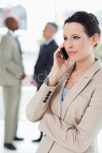 Serious businesswoman talking on a mobile phone with executives behind her Stock photo © wavebreak_media