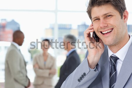 Smiling businessman looking at the camera in front of his team Stock photo © wavebreak_media