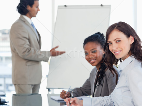 Young smiling executives working while listening to a presentation Stock photo © wavebreak_media
