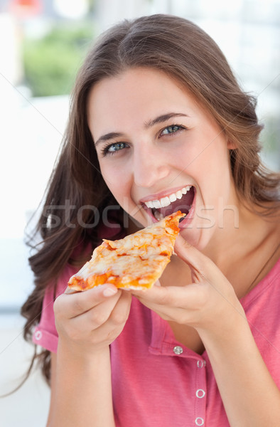 A woman looking at the camera in front of her as she is about to eat her pizza Stock photo © wavebreak_media