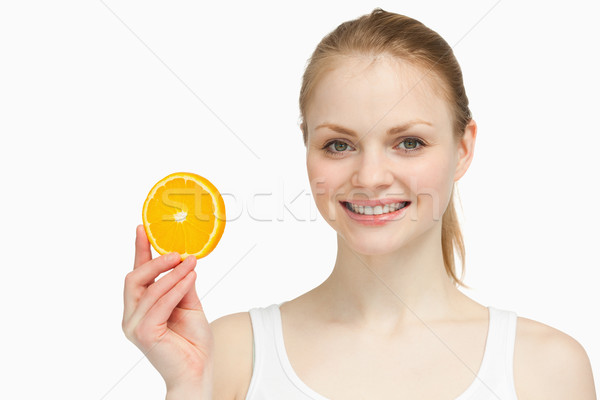 Cheerful woman presenting an orange slice against white background Stock photo © wavebreak_media