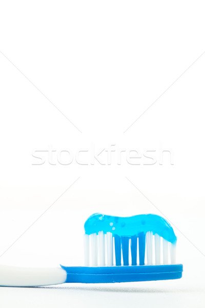 Blue toothpaste on a toothbrush against white background Stock photo © wavebreak_media