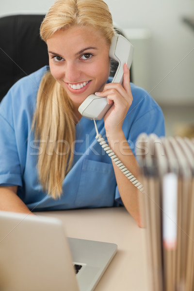 Blonde nurse calling while looking at camera in hospital reception Stock photo © wavebreak_media