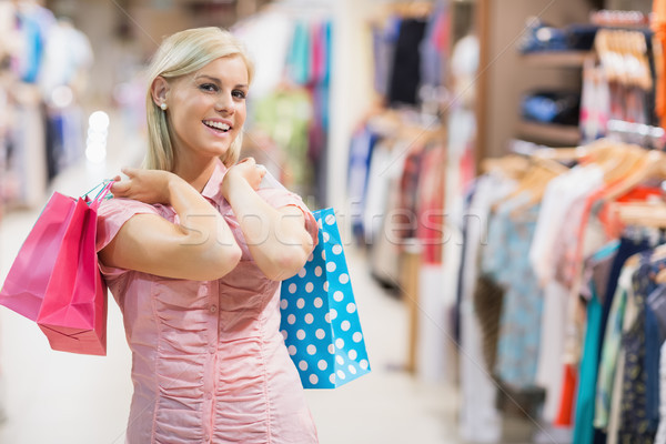 Woman smiling in clothes shop holding two bags Stock photo © wavebreak_media