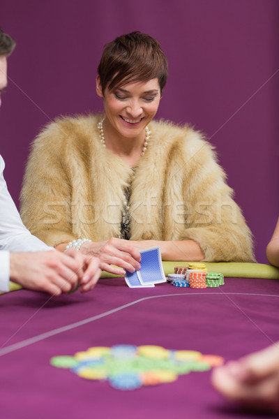 Woman smiling looking at her cards at the casino Stock photo © wavebreak_media