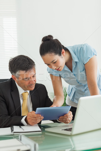 Man and woman working together on a digital tablet and a laptop in an office Stock photo © wavebreak_media