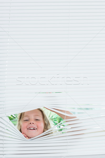 Stock photo: Smiling girl peeking out of white blinds
