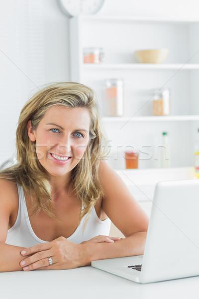Sorrindo laptop sessão cozinha computador mulher Foto stock © wavebreak_media