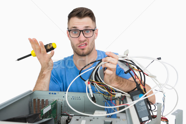 Portrait of confused it professional with screw driver and cable Stock photo © wavebreak_media