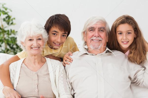 дедушка и бабушка внучата портрет улыбаясь диван дома Сток-фото © wavebreak_media