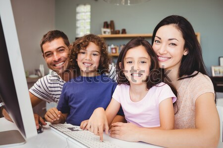 Happy family looking at the camera with a laptop Stock photo © wavebreak_media