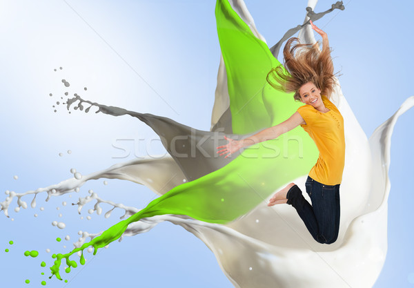 Pretty young woman jumping for joy with artistic paint splashes Stock photo © wavebreak_media