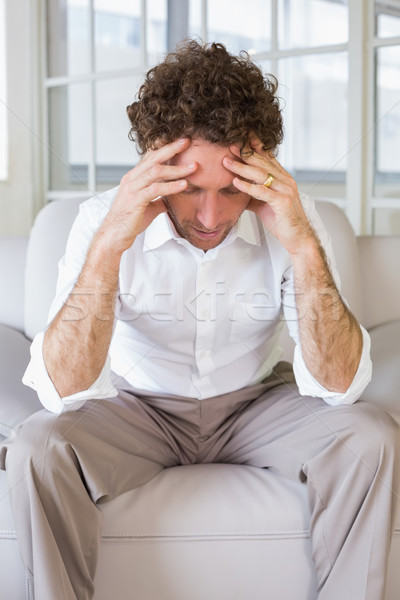 Worried well dressed man sitting with head in hands on sofa in t Stock photo © wavebreak_media