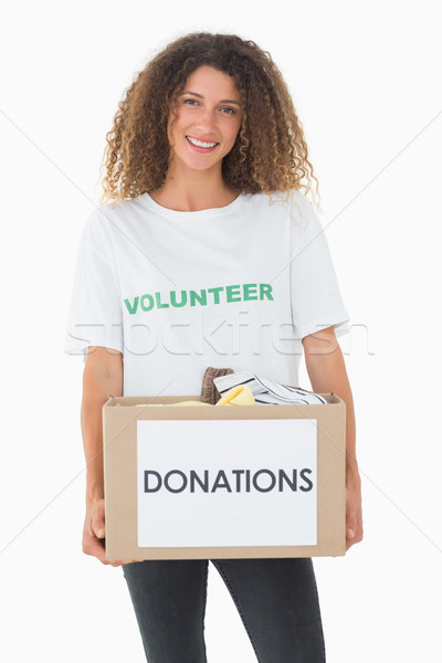 Smiling volunteer holding a box of donations Stock photo © wavebreak_media
