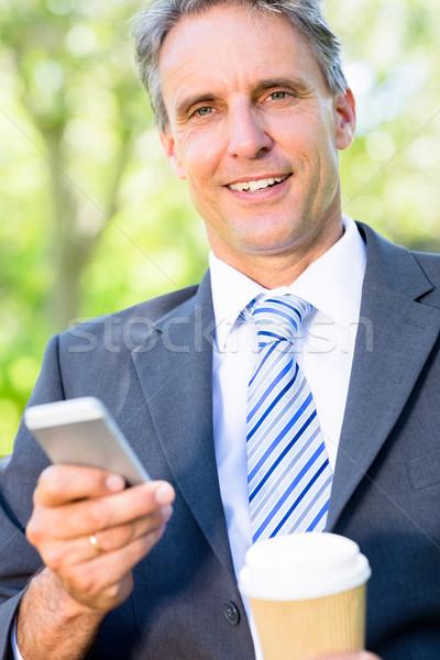 Empresario teléfono móvil desechable taza retrato sonriendo Foto stock © wavebreak_media