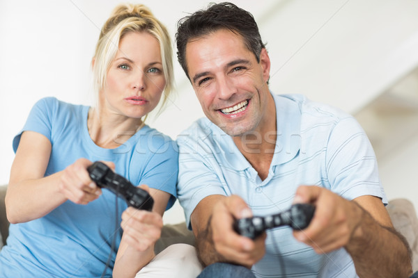 Stock photo: Cheerful couple playing video games in living room