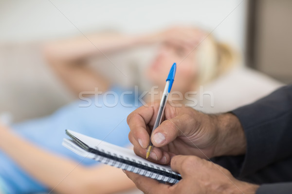 Hands writing diary with blurred woman in background Stock photo © wavebreak_media