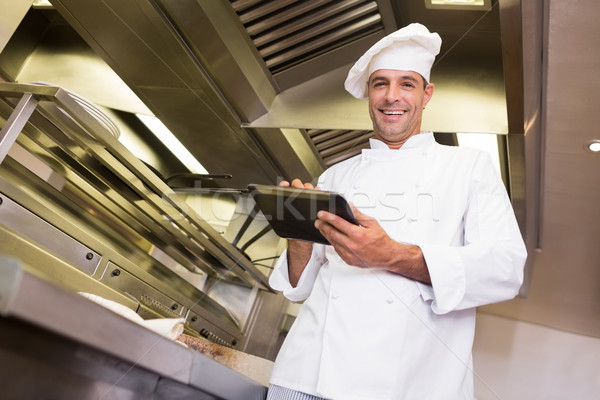 Smiling male cook using digital tablet in kitchen Stock photo © wavebreak_media