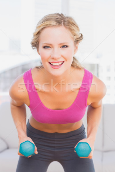 Fit blonde lifting dumbbells and smiling at camera Stock photo © wavebreak_media