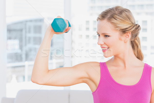 Fit blonde lifting dumbbell and flexing Stock photo © wavebreak_media