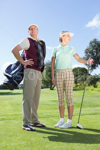 Golfing couple standing and looking around Stock photo © wavebreak_media
