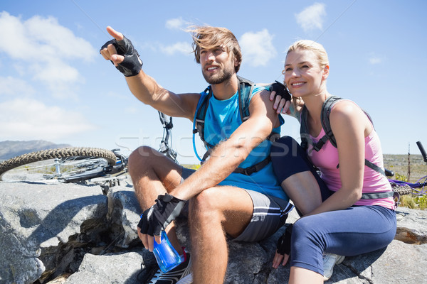 Fit cyclist couple taking a break on rocky peak  Stock photo © wavebreak_media