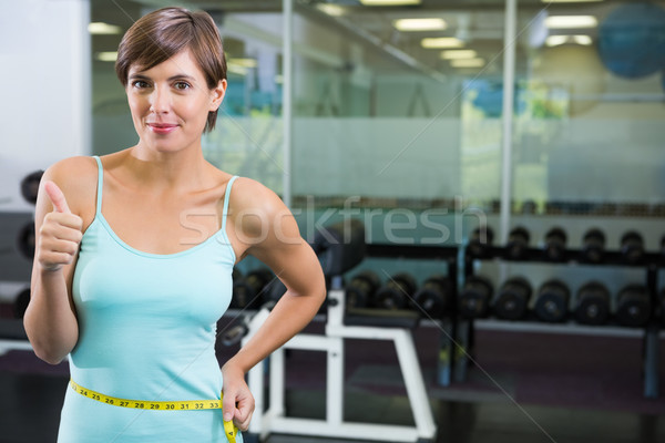 Fit brunette smiling at camera with measuring tape around waist Stock photo © wavebreak_media