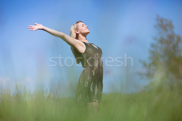 Pretty blonde in sundress standing with arms out Stock photo © wavebreak_media