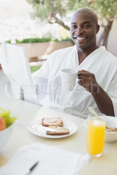 Homem bonito roupão de banho café da manhã fora casa Foto stock © wavebreak_media