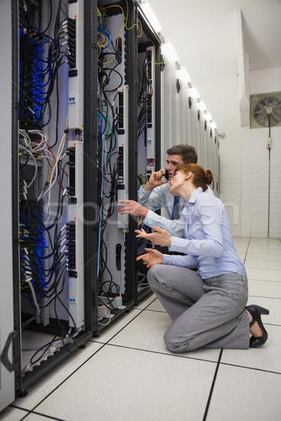 Team of technicians kneeling and looking at servers Stock photo © wavebreak_media