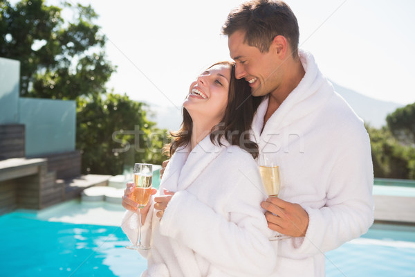 Cheerful couple with champagne flutes by swimming pool Stock photo © wavebreak_media