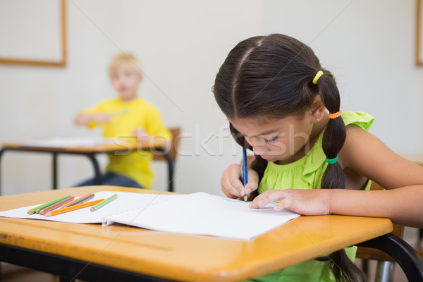 Stock photo: Cute pupils colouring at desks in classroom
