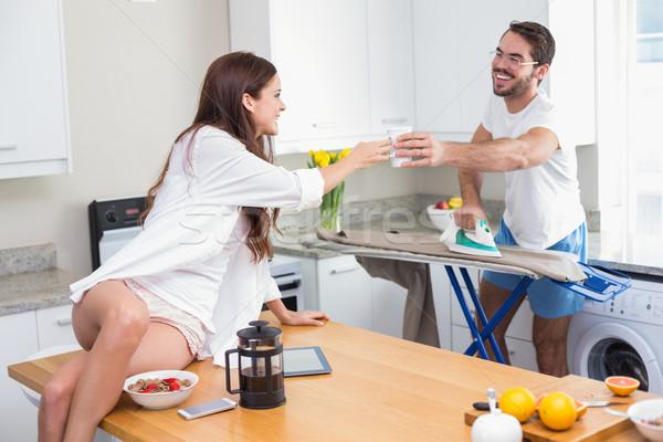 Pretty brunette passing her boyfriend a coffee Stock photo © wavebreak_media