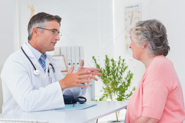 Stock photo: Male doctor conversing with female patient at table