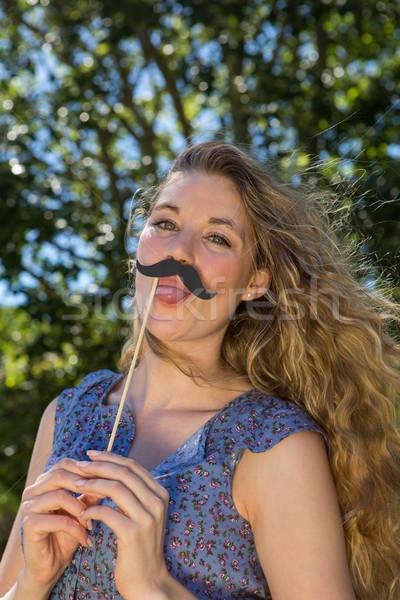Pretty blonde with fake mustache Stock photo © wavebreak_media