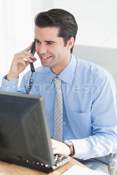 Businessman having phone call while using his laptop Stock photo © wavebreak_media