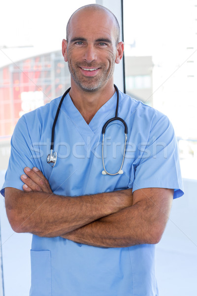 Smiling male doctor looking at camera with arms crossed Stock photo © wavebreak_media
