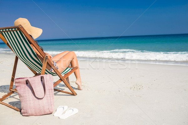 c704069b87 Side view of pretty brunette relaxing on deck chair at the beach ...