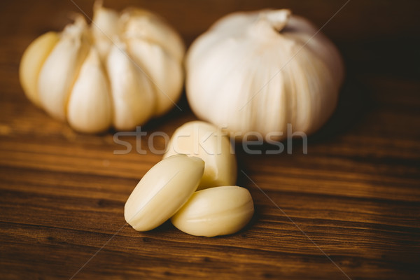 Garlic cloves and bulb on chopping board Stock photo © wavebreak_media