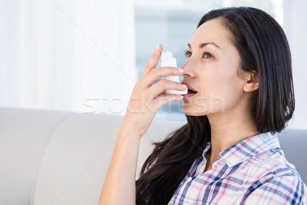 Pretty brunette using inhaler on couch Stock photo © wavebreak_media