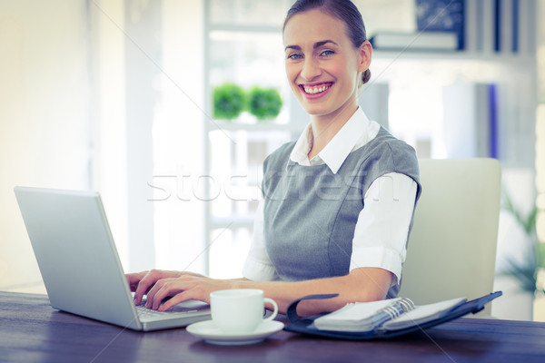 Happy businesswoman working on laptop computer and looking at ca Stock photo © wavebreak_media