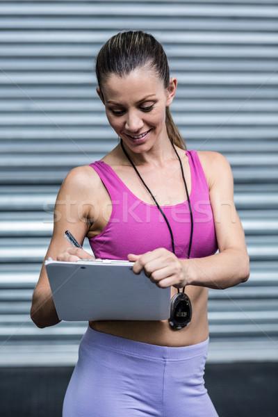 Femenino entrenador escrito portapapeles sonriendo bloc de notas Foto stock © wavebreak_media