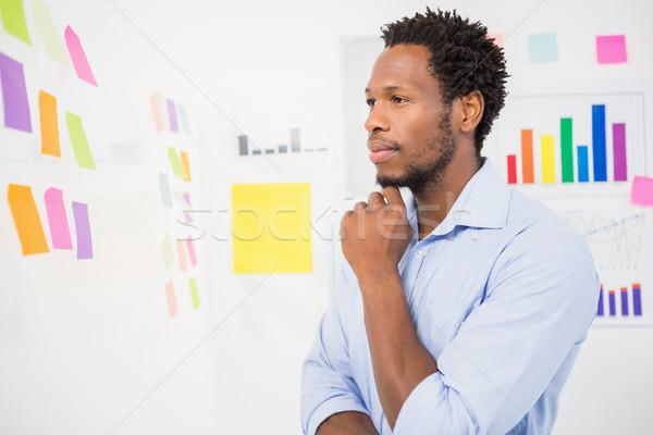 Fiatal komoly üzletember néz cetlik iroda Stock fotó © wavebreak_media