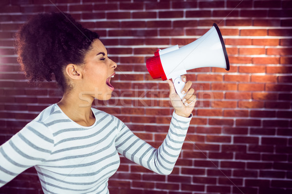 Young woman using her megaphone in the light  Stock photo © wavebreak_media