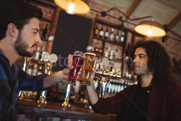 Friends toasting glasses of beer at bar counter Stock photo © wavebreak_media