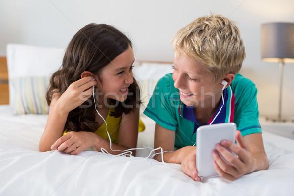 Testvérek zenét hallgat mobiltelefon ágy otthon zene Stock fotó © wavebreak_media