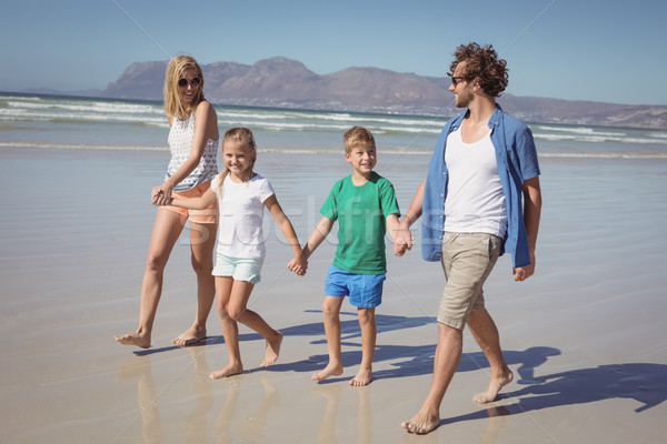 Happy family holding hands while walking at beach Stock photo © wavebreak_media