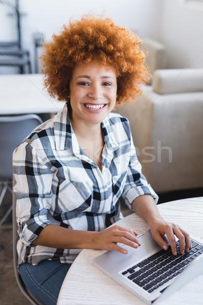 Portrait of smiling businesswoman using laptop at office Stock photo © wavebreak_media