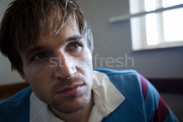 Close up of thoughtful rugby player looking away while sitting against wall Stock photo © wavebreak_media