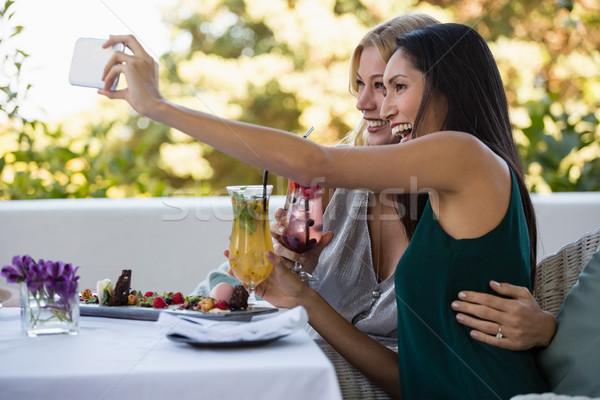 Cheerful friends taking selfie while holding drinks Stock photo © wavebreak_media